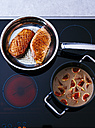 Fried duck breast and pot of fig sauce on cook top - PPXF00048