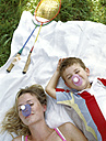Portrait of smiling mother and little son with shuttlecocks on their noses lying on blanket - FSF00874