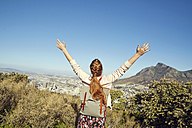 South Africa, Cape Town, Signal Hill, happy young woman with raised arms overlooking the city - SRYF00516