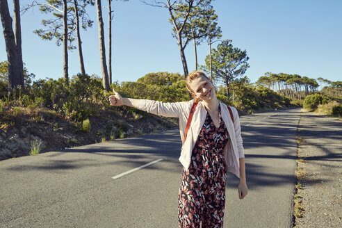 South Africa, Cape Town, Signal Hill, happy young woman hitchhiking on country road - SRYF00519