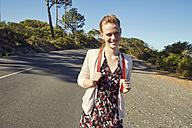 South Africa, Cape Town, Signal Hill, smiling young woman with backpack on country road - SRYF00525