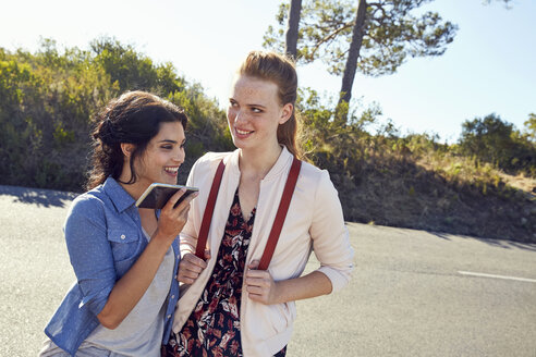 South Africa, Cape Town, Signal Hill, two smiling young women with cell phone on a trip - SRYF00528