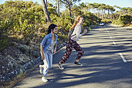 South Africa, Cape Town, Signal Hill, two happy young women crossing country road - SRYF00534