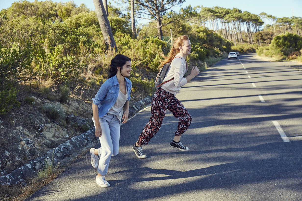 South Africa, Cape Town, Signal Hill, two happy young women crossing country road - SRYF00534 - Martina Ferrari/Westend61