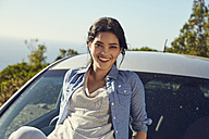 Smiling young woman at a car - SRYF00537