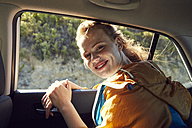 Smiling young woman on the back seat of a car - SRYF00543