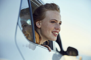 Smiling young woman looking out of a car - SRYF00546