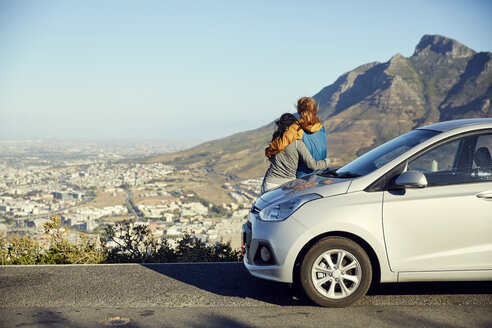 South Africa, Cape Town, Signal Hill, two young women leaning against car overlooking the city - SRYF00549