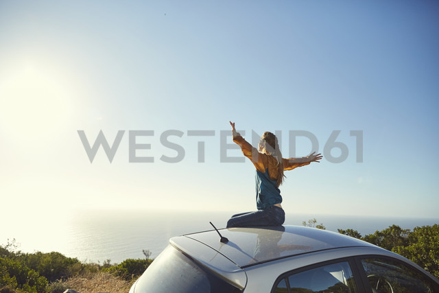 South Africa, Cape Town, Signal Hill, young woman sitting on top of car enjoying the view to the sea - SRYF00552 - Martina Ferrari/Westend61