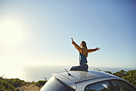 South Africa, Cape Town, Signal Hill, young woman sitting on top of car enjoying the view to the sea - SRYF00552
