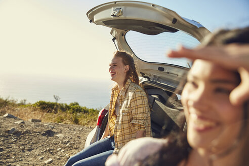 South Africa, Cape Town, Signal Hill, two happy young women at a car at the coast - SRYF00555