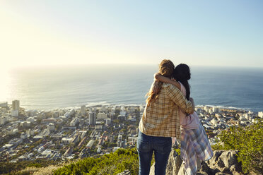 South Africa, Cape Town, Signal Hill, two young women hugging overlooking the city and the sea - SRYF00561