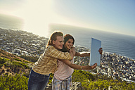 South Africa, Cape Town, Signal Hill, two young women above the city taking a selfie with tablet - SRYF00564