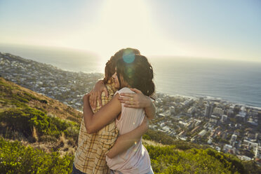 South Africa, Cape Town, Signal Hill, two young women hugging above the city - SRYF00567
