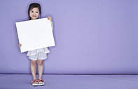 Portrait of smiling little girl holding white cardboard in front of purple background - FSF00902