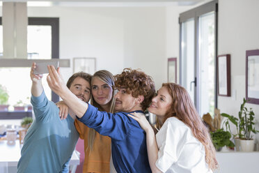Friends taking selfies in kitchen - ZOCF00362