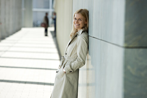 Portrait of smiling blond woman wearing trench coat leaning against facade - CHAF01874