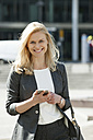 Portrait of smiling blond businesswoman with cell phone and handbag - CHAF01877