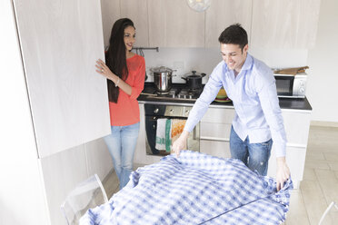 Smiling couple in kitchen preparing dining table - FMOF00282