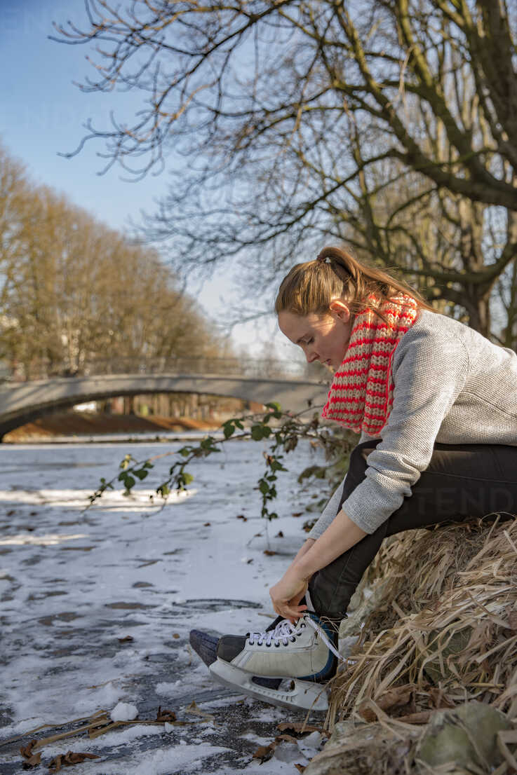 Woman putting on ice skates at canal - MFF03506 - Mareen Fischinger/Westend61