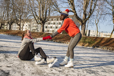 Woman helping ice skating friend getting up on canal - MFF03515