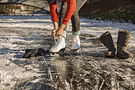 Close-up of woman putting on ice skates on canal - MFF03518