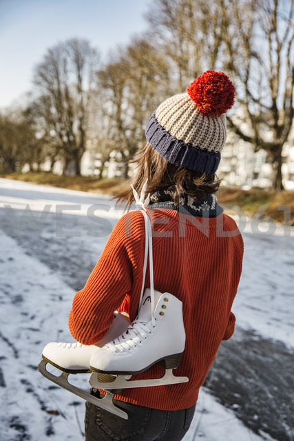 Woman on canal carrying ice skates - MFF03521