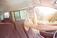 Happy young woman driving car - ZOCF00375