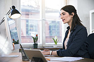 Woman working at desk in office - FKF02245