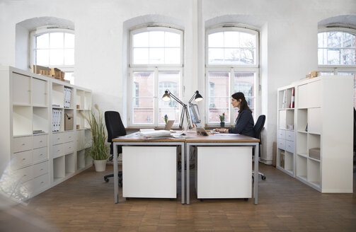 Woman working at desk in office - FKF02248