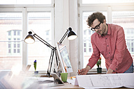 Man working on blueprint at desk in office - FKF02263