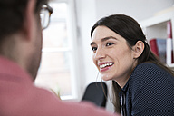 Smiling woman looking at man in office - FKF02266