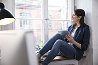 Woman with tablet looking out of window in office - FKF02275