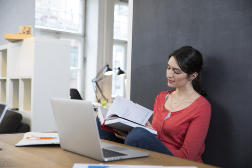 Woman with book and laptop at desk in office - FKF02284