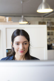 Smiling woman looking at computer screen at desk in office - FKF02299