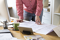 Close-up of man working on blueprint at desk in office - FKF02305