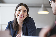 Smiling woman looking at man in office - FKF02308
