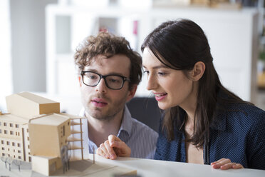Man and woman discussing architectural model in office - FKF02317