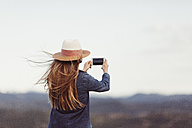 Back view of redheaded woman taking picture with smartphone in  nature - JPF00206