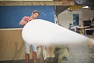 Surfboard shaper workshop, man checking surfboard - ZEF13672