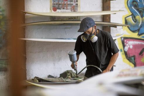 Surfboard shaper workshop, surfboard shop employee spraying surfboard - ZEF13678