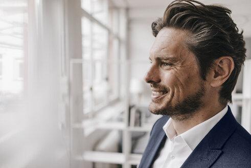 Smiling businessman at the window - KNSF01261