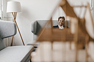 Smiling man on couch with architectural model in foreground - KNSF01276
