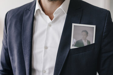 Businessman with instant photo in pocket of his jacket - KNSF01279