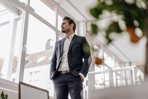 Confident businessman standing in office - KNSF01285