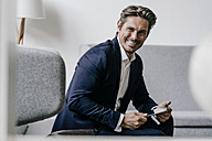 Smiling businessman with tablet on couch - KNSF01291