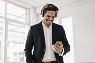 Smiling businessman with cell phone and headphones - KNSF01297