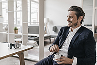 Smiling businessman having a coffee break - KNSF01300