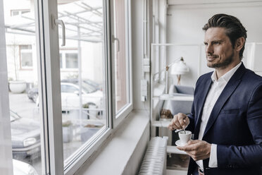 Businessman having a coffee at the window - KNSF01303