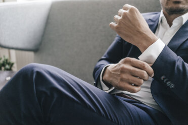 Close-up of businessman adjusting his sleeves - KNSF01306